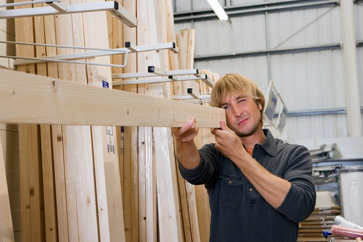 Oswald Wholesale Lumber Man checking straightness of timber in DIY store