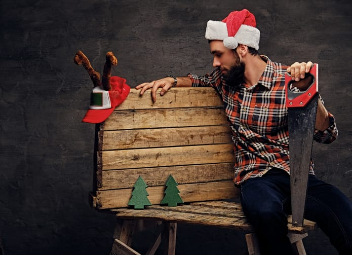 Oswald Wholesale Lumber Christmas and New Year scene. Bearded male in Santa's hat sits on wooden palette with fir trees and holds handsaw.